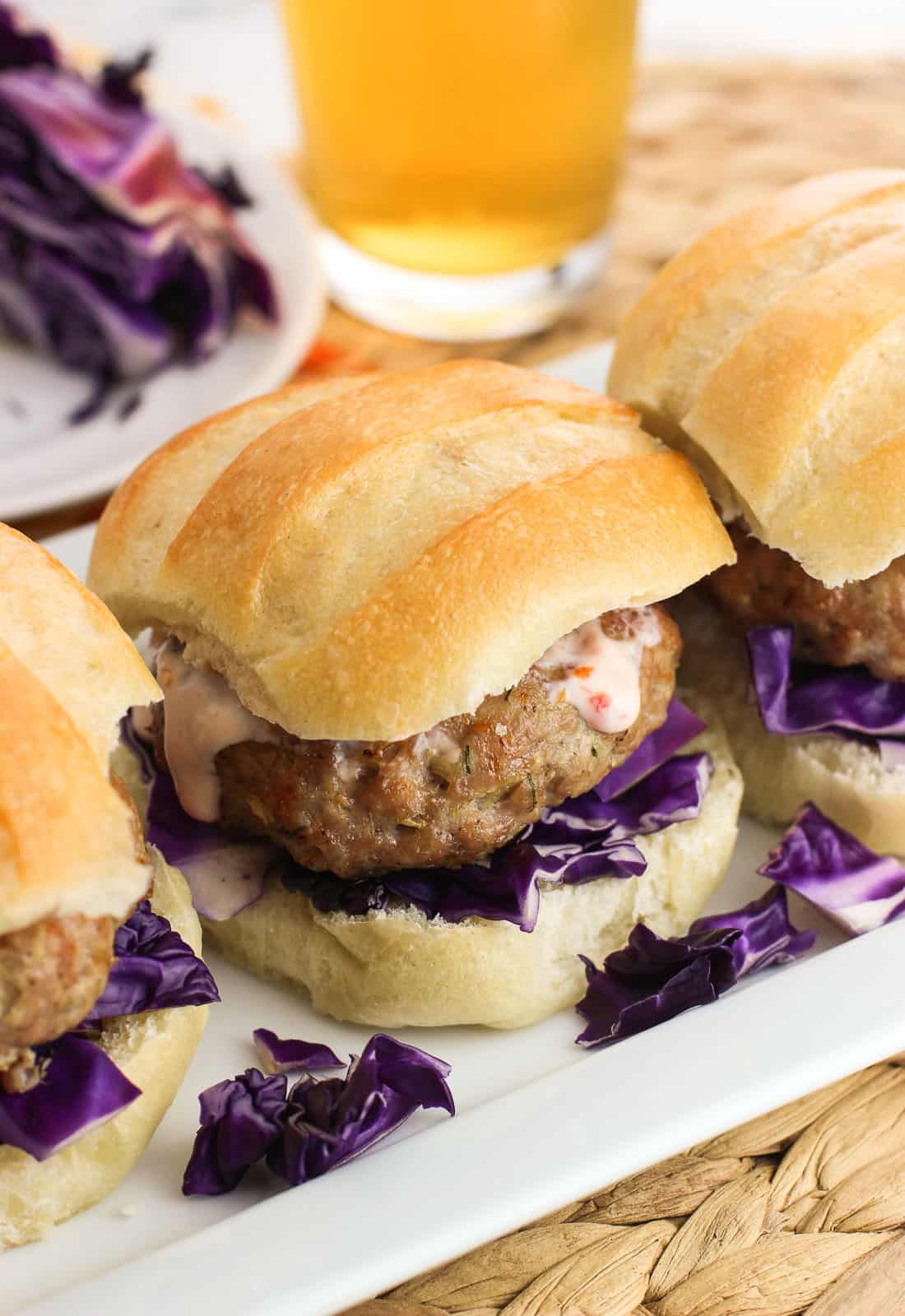 Three pork burger sliders on a rectangular tray, each on slider buns with red cabbage and chili garlic sauce