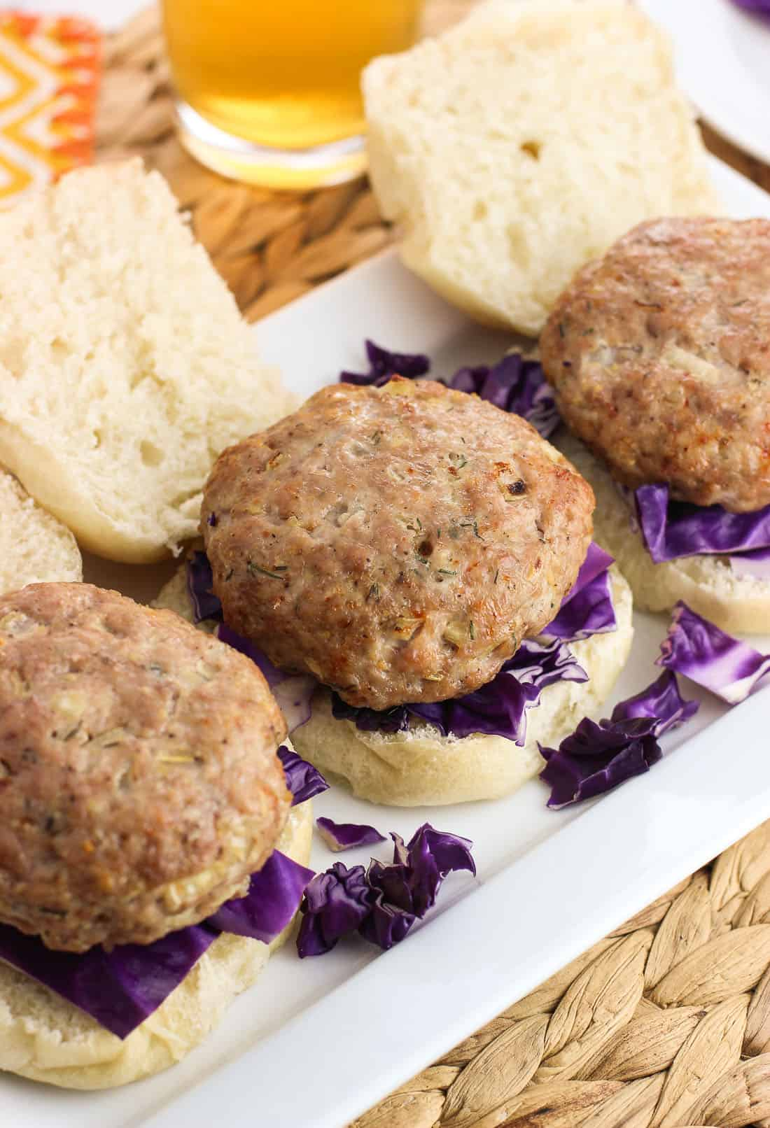 Open face pork burgers on small buns with red cabbage underneath the patties