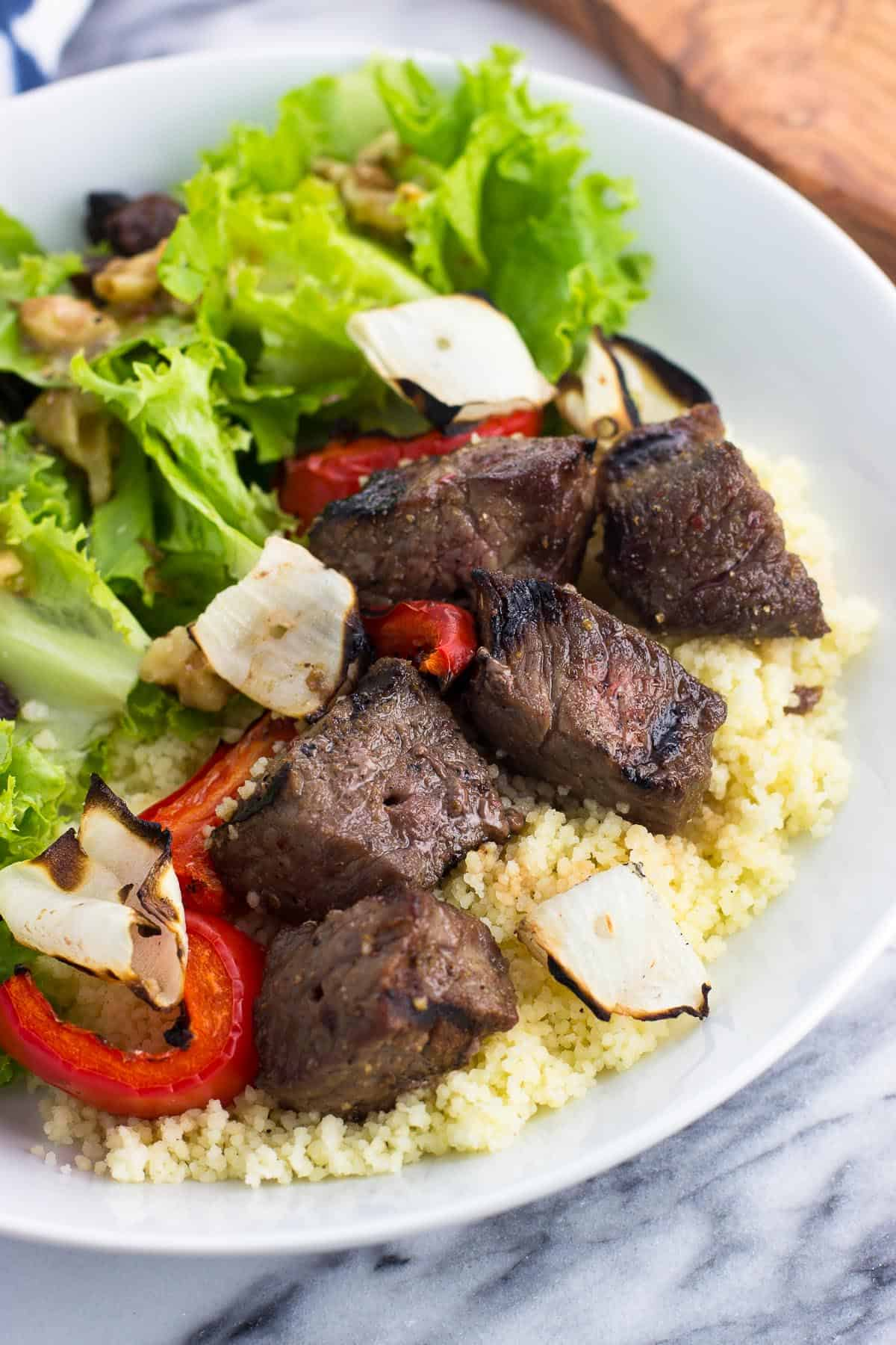 Grilled steak cubes served over couscous with grilled vegetables and a side salad