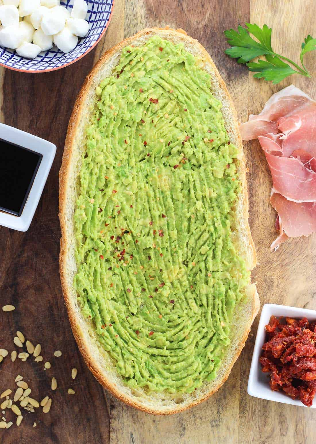 Mashed avocado on a half-loaf of garlic bread on a wooden board surrounded by toppings