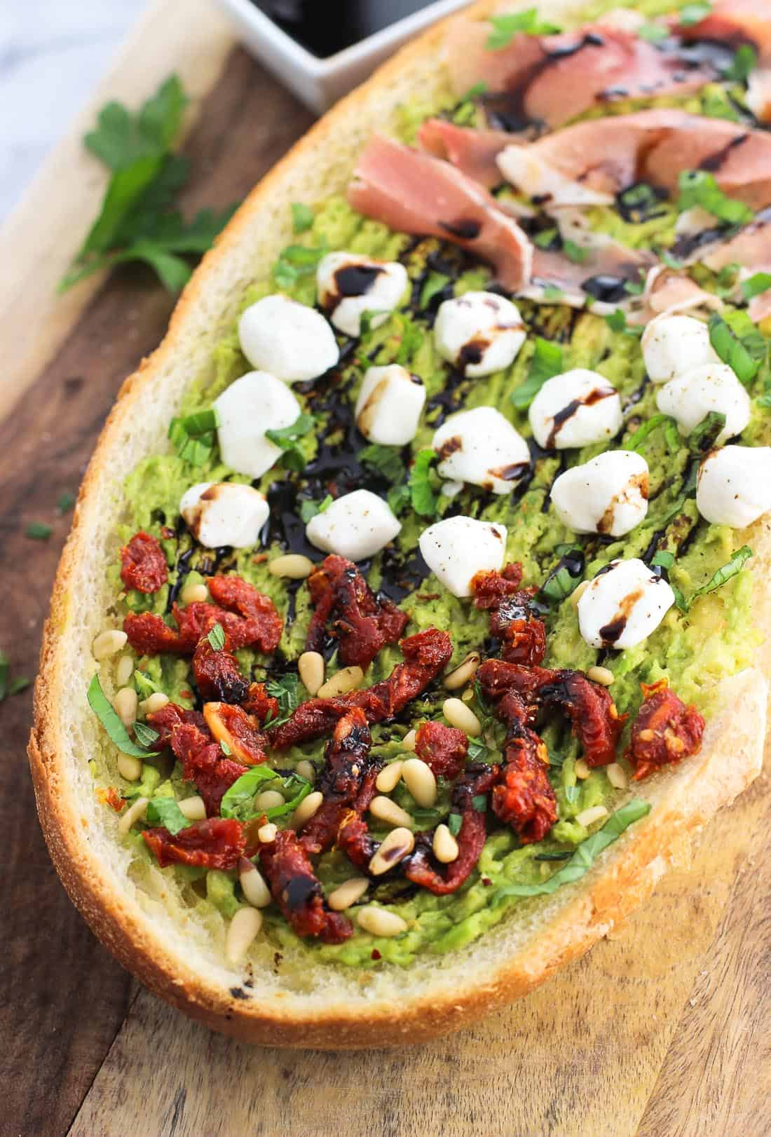A slab of avocado garlic bread with various toppings.