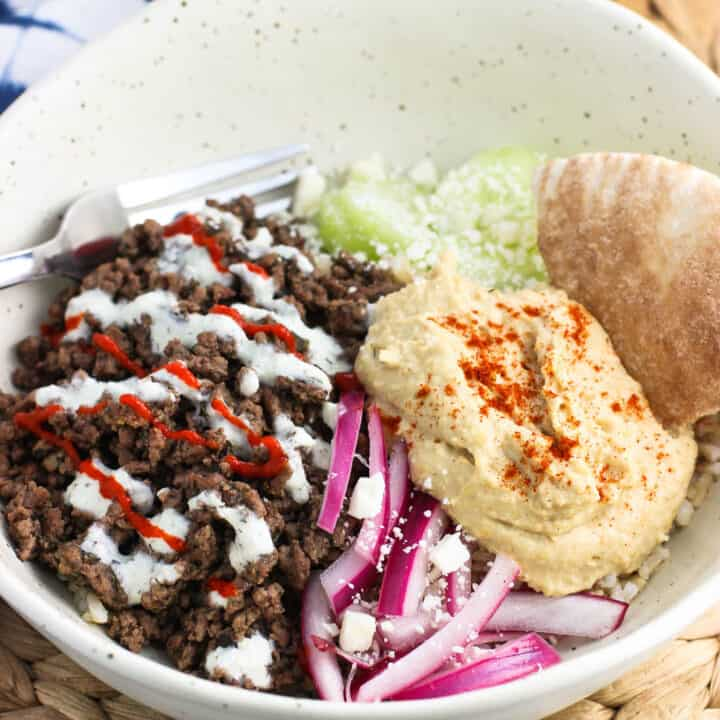 Spiced beef, hummus, cucumber slices, yogurt sauce, pickled red onion, and feta are served over brown rice for a loaded Mediterranean Beef Rice Bowl recipe that will fill you up. This healthy dinner or lunch is easily customizable.