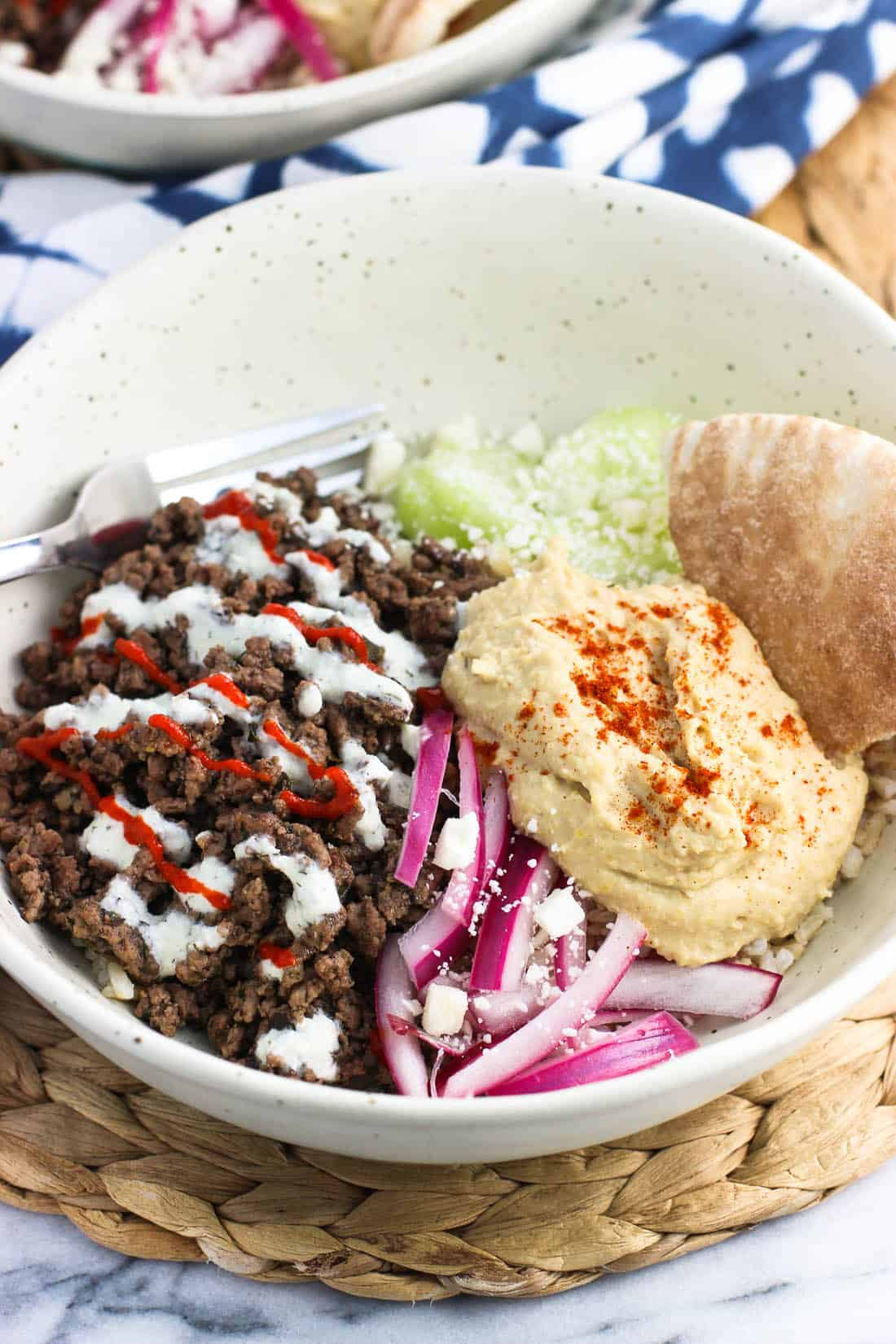 A shallow bowl filled with spiced ground beef, cucumber slices, yogurt sauce, feta, red onions, hummus, and pita