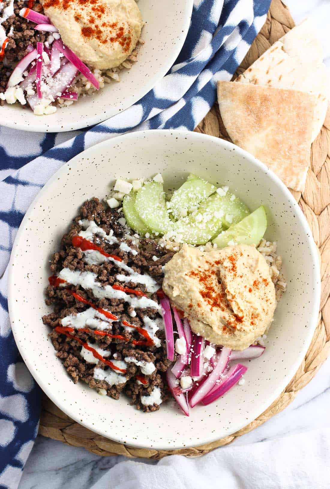 An overhead picture of a rice bowl featuring spiced beef, red onion, hummus, and cucumber slices