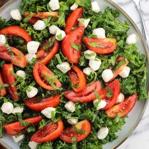 An overhead picture of kale, tomatoes, mozzarella pearls, and basil on a large plate next to a fork and salt and pepper shakers