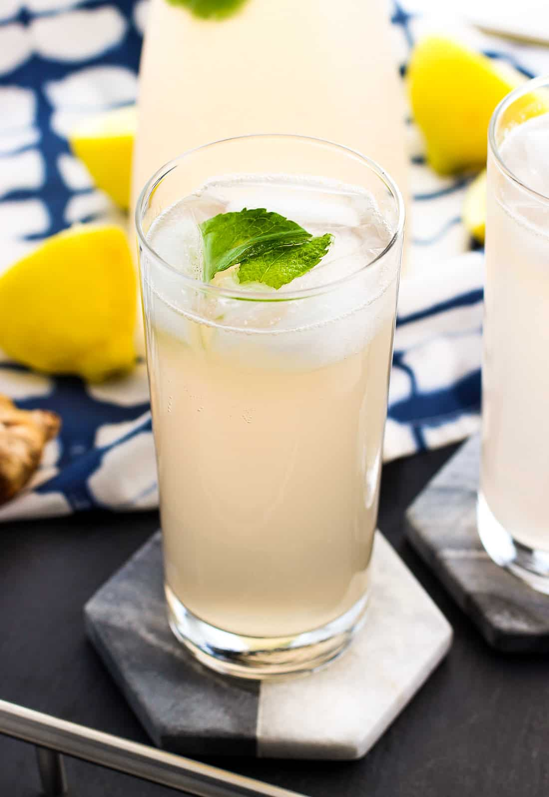 A tall glass of ginger lemonade on a marble coaster filled with ice and garnished with fresh mint leaves in front of lemons and a piece of ginger root