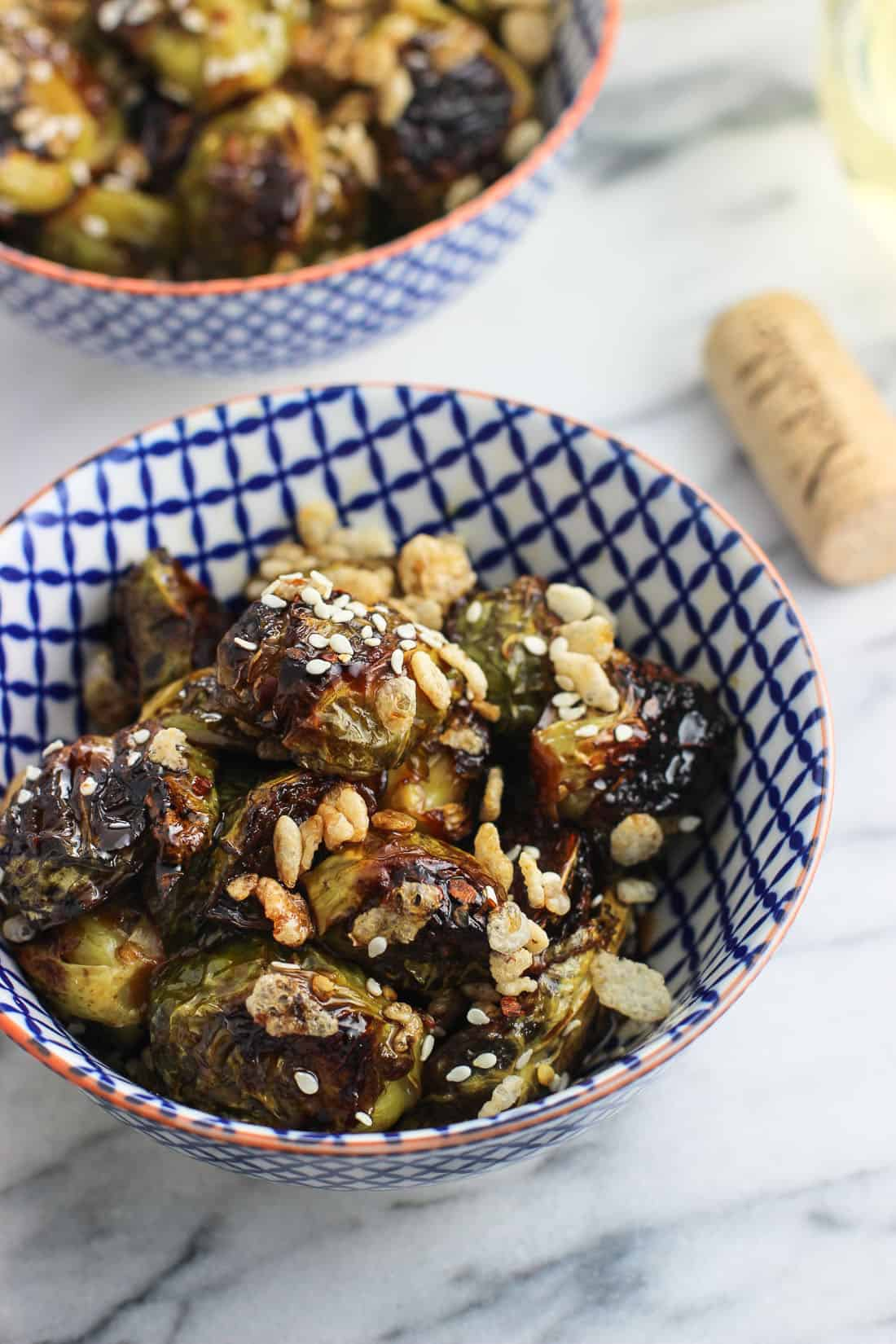 A close-up of a bowl of roasted Brussels sprouts topped with crisped rice with a wine cork and another bowl in the background