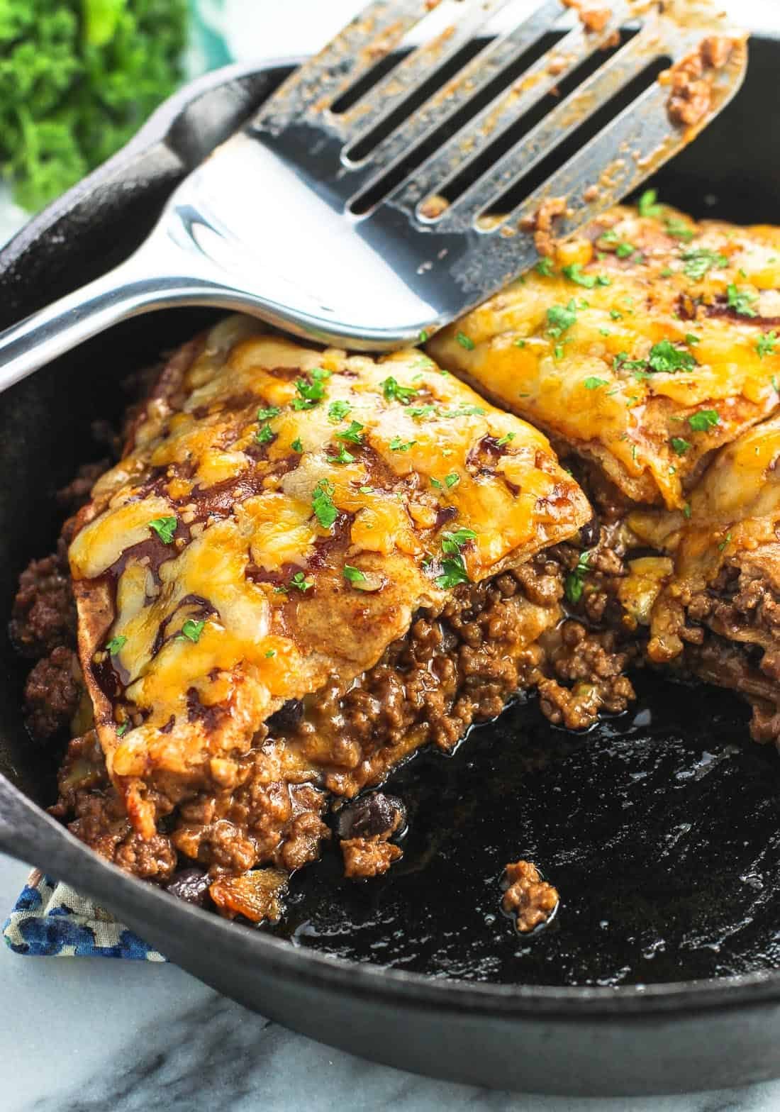 Beef tortilla pie in a cast iron skillet with one wedge removed, with a metal spatula resting on top