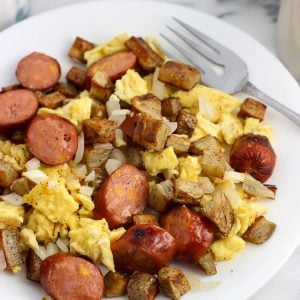A serving of the sausage and egg scramble on a plate with a fork.