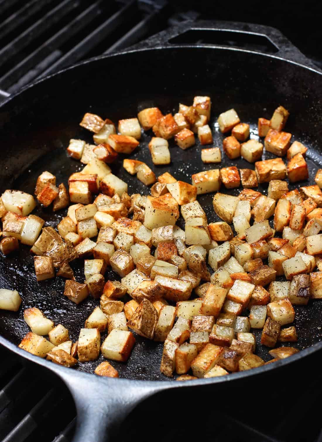 A cast iron pan filled with roasted potato cubes on a grill.