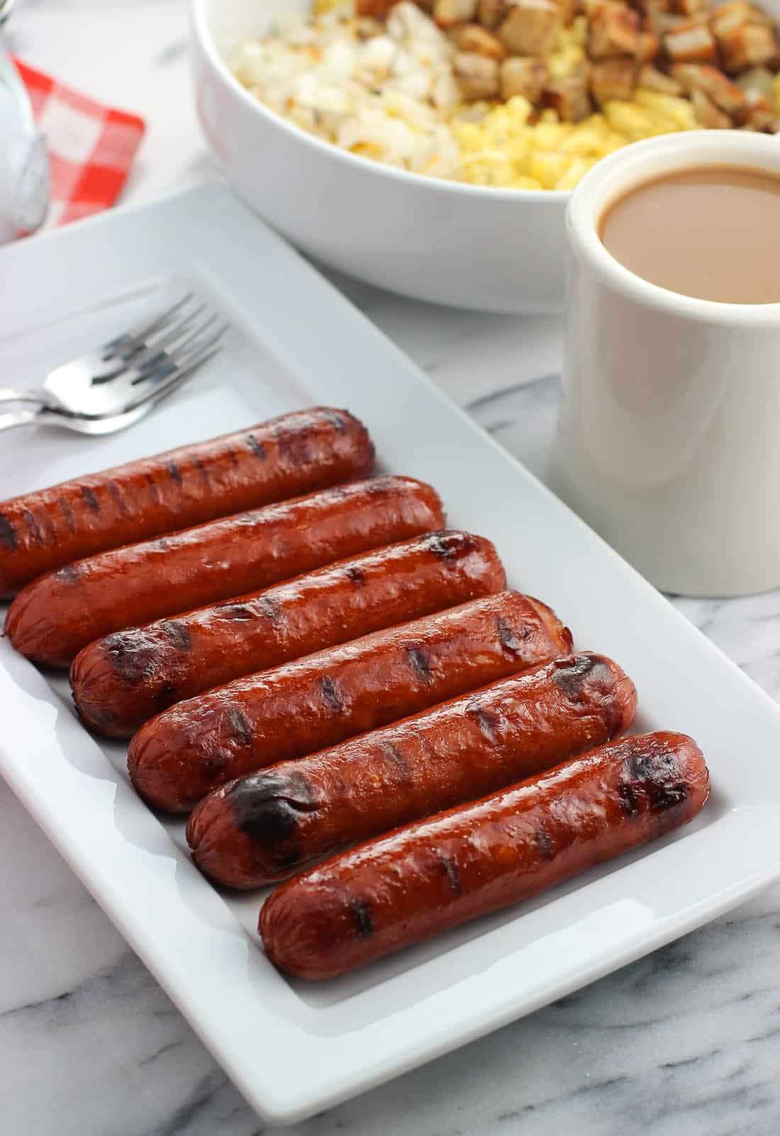 Six grilled smoked sausage links on a rectangular tray.