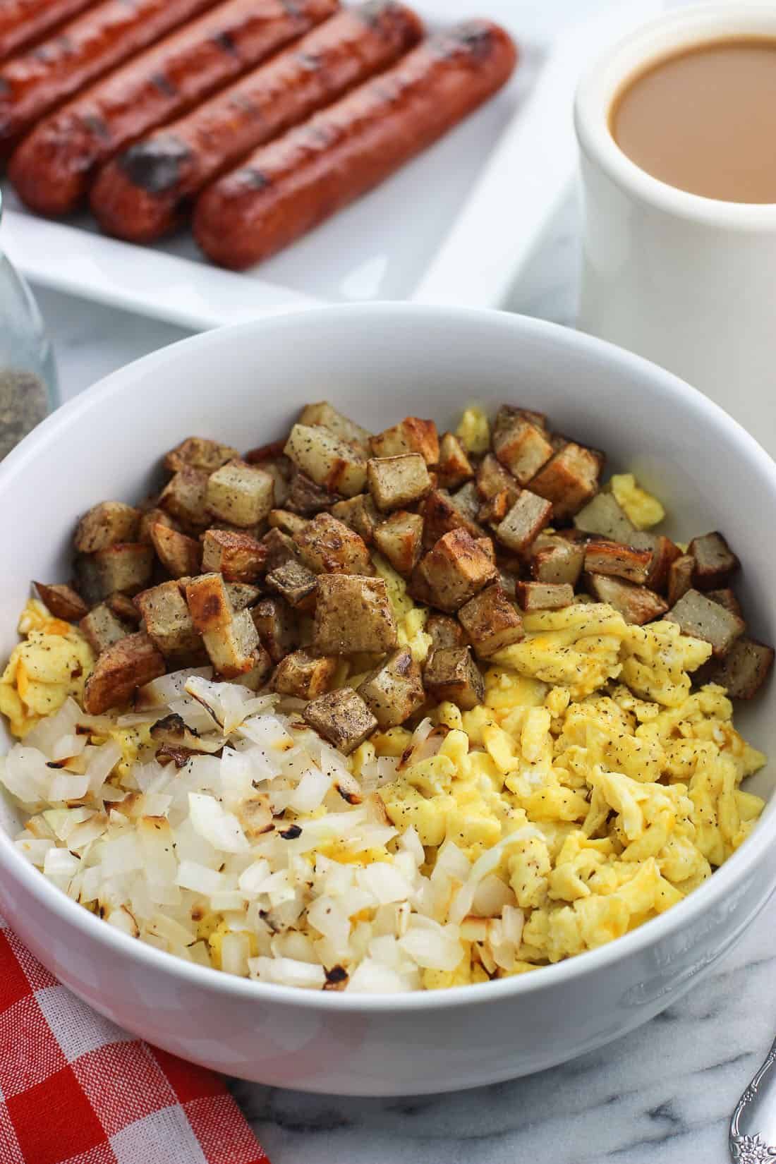 A big bowl featuring sections of grilled onion, scrambled eggs, and roasted potatoes.