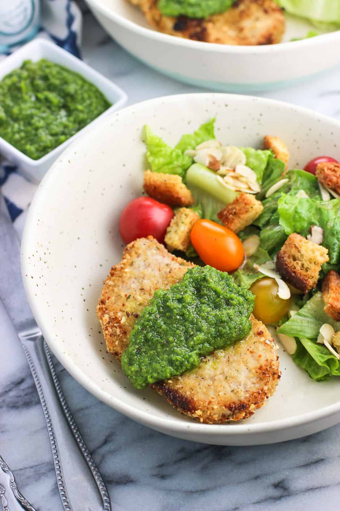Parmesan almond crusted pork chops are baked and topped with parsley pesto for a relatively quick and easy main dish recipe.