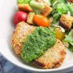 A crusted baked pork chop on a dish served with a dollop of pesto next to a side salad