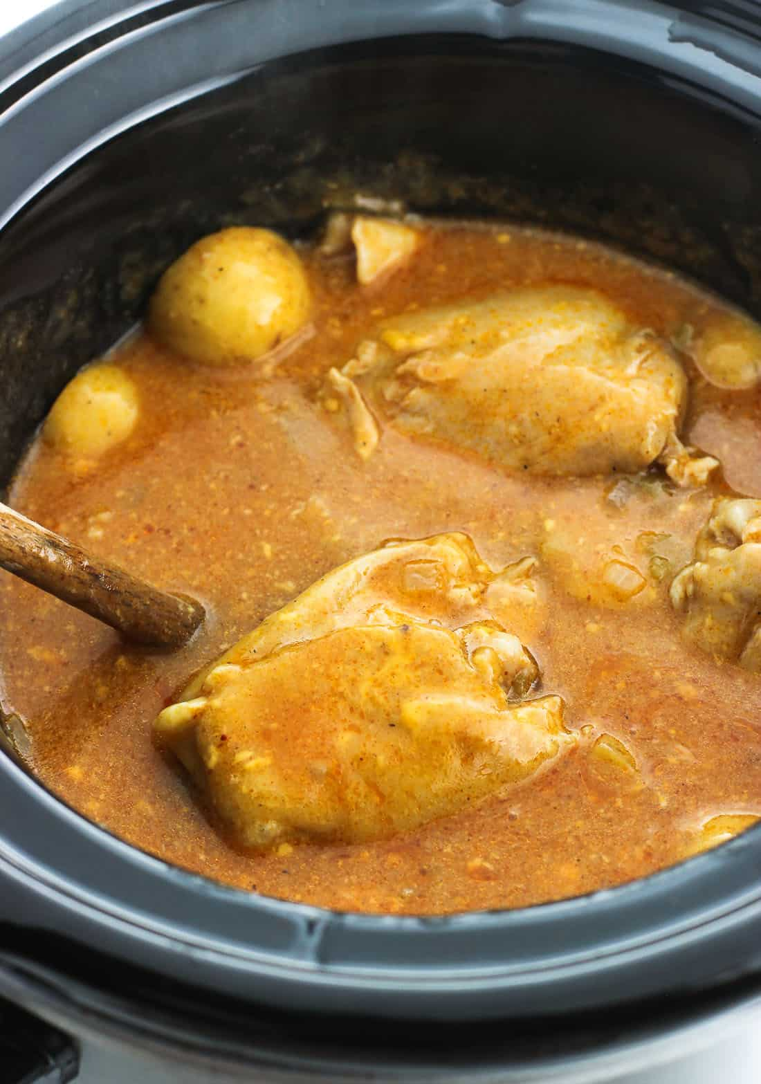 A spoon in a slow cooker filled with sauce and cooked chicken and potatoes.