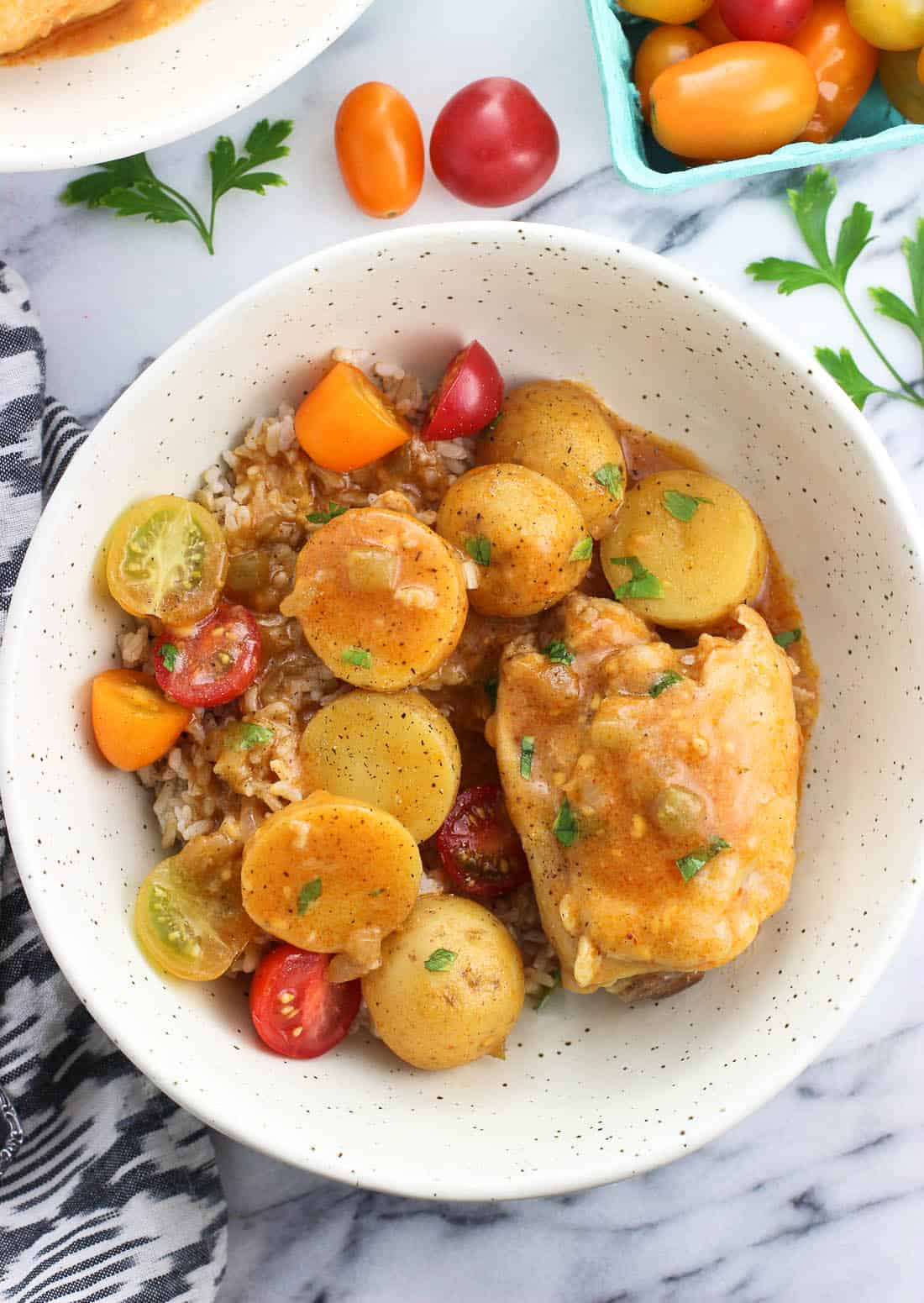 A serving of chicken, potatoes, and tomatoes in a dinner bowl over rice.