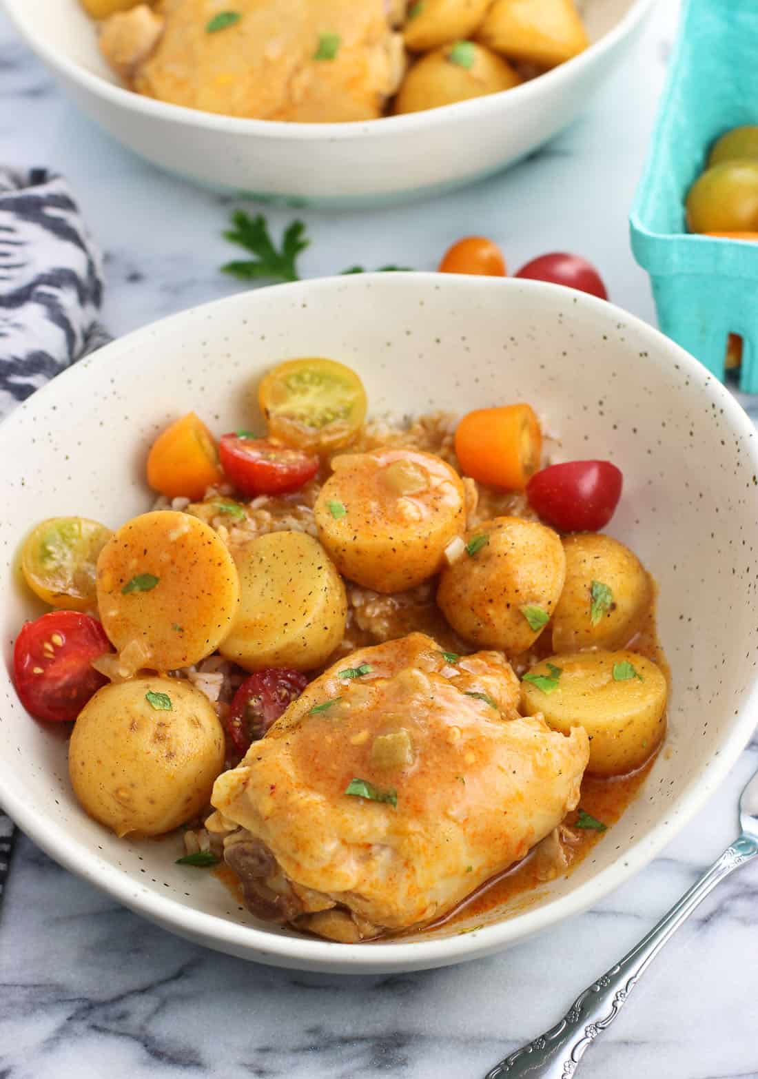 A chicken thigh, roasted potatoes, tomatoes, and sauce in a dinner bowl.