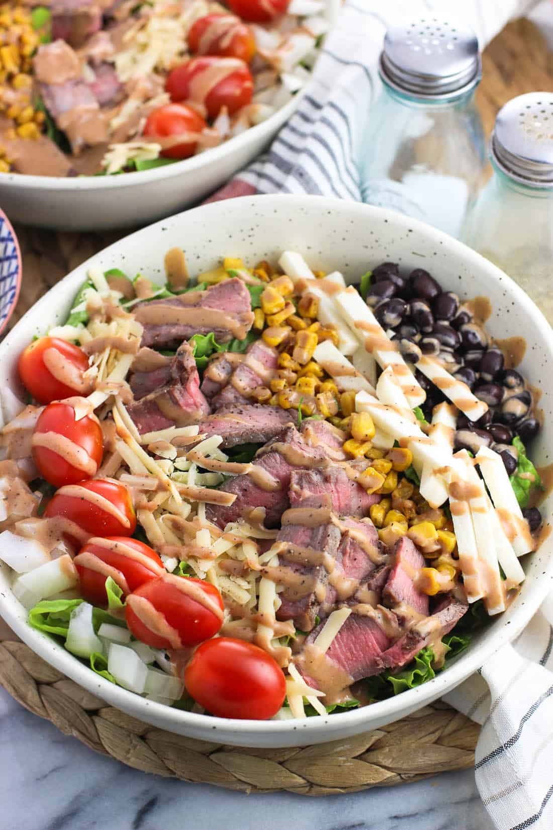 A steak salad with toppings arranged in neat lines on top.