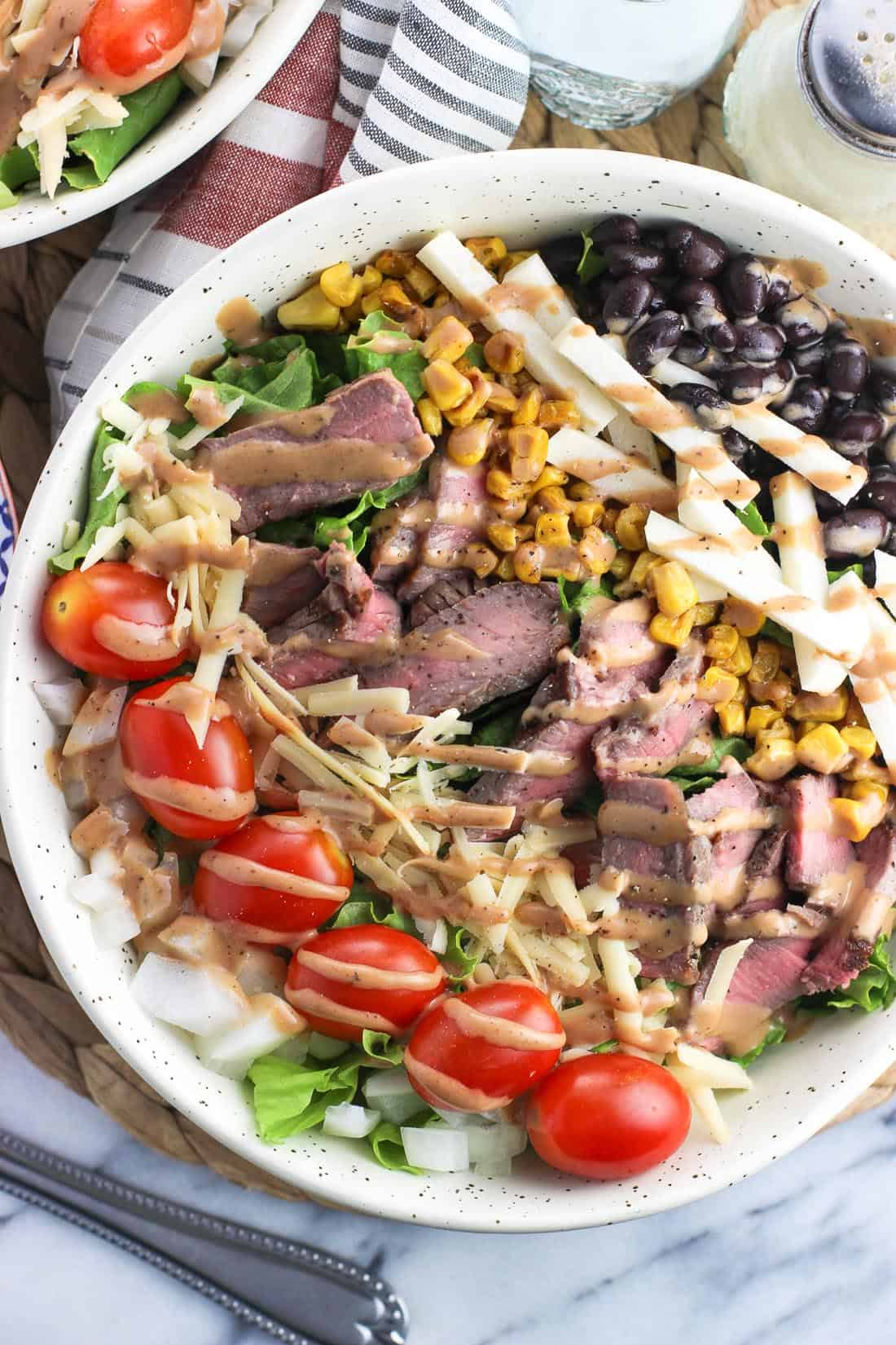 A steak salad in a large bowl with many toppings and drizzled with BBQ ranch dressing.