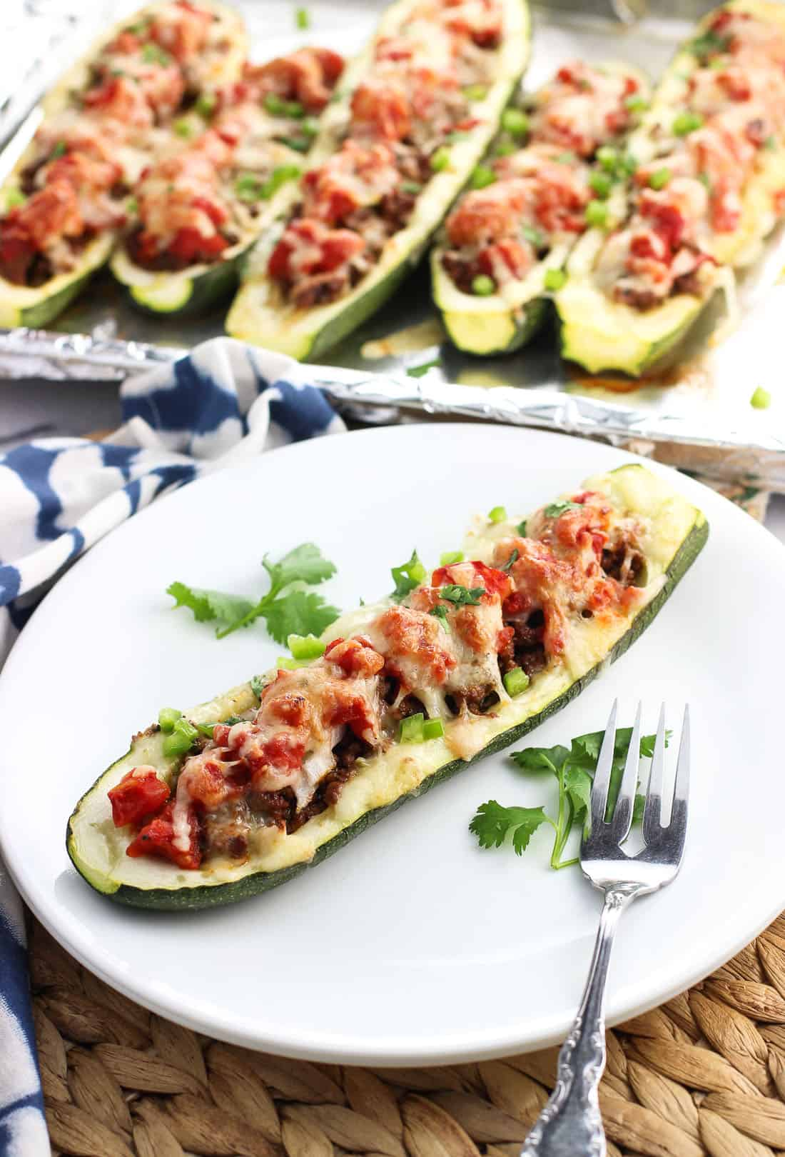 One taco zucchini boat on a plate with a fork with more zucchini halves on the baking sheet in the background