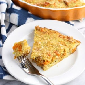 A slice of zucchini pie on a plate with a piece speared on a fork.
