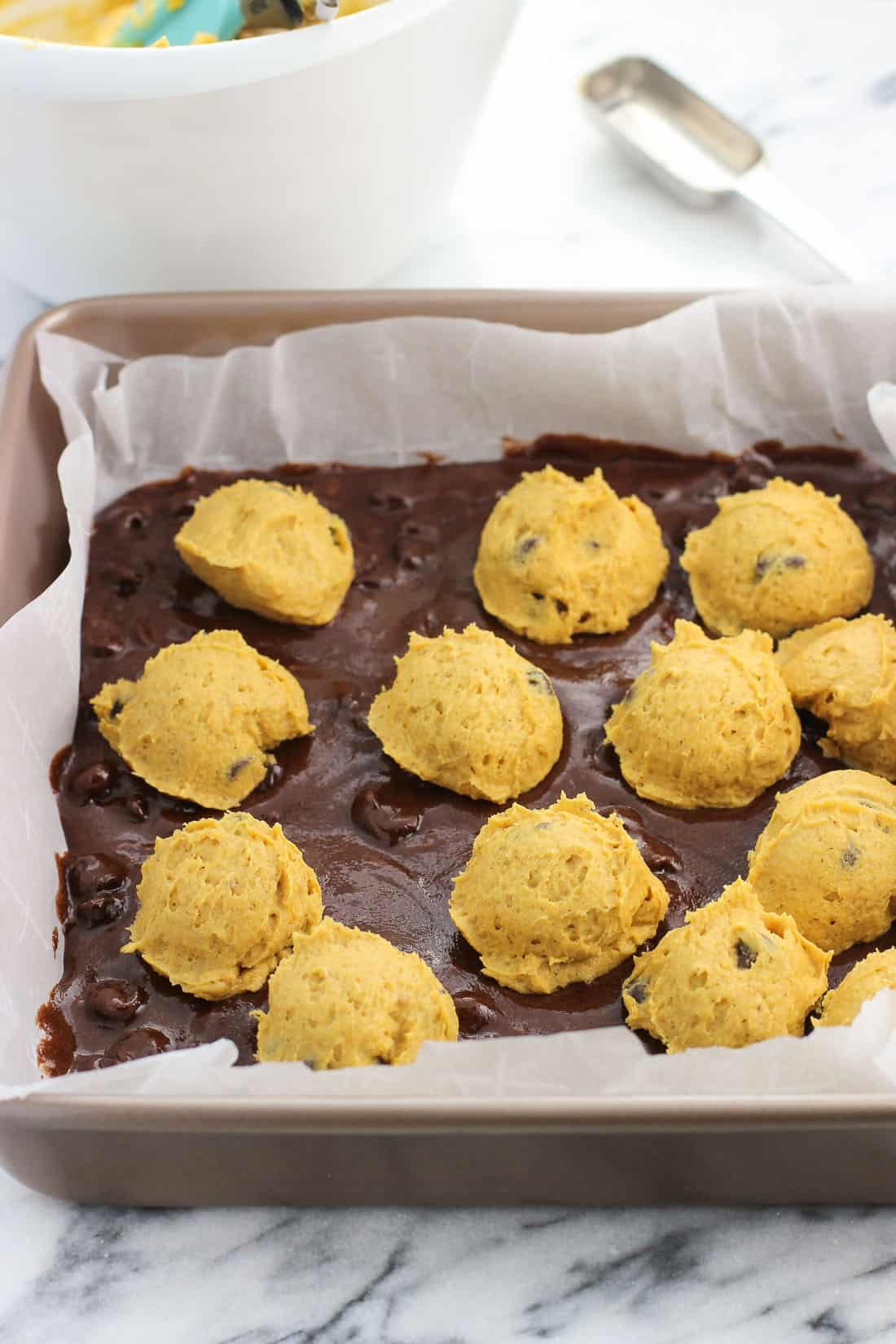 Brownie batter in a parchment-lined baking dish with globs of pumpkin batter scattered on top before being swirled in