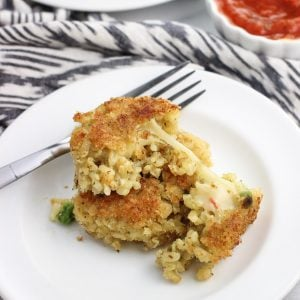 Two risotto cakes on an appetizer plate, with the top cake cut in half to see the cheese melting out