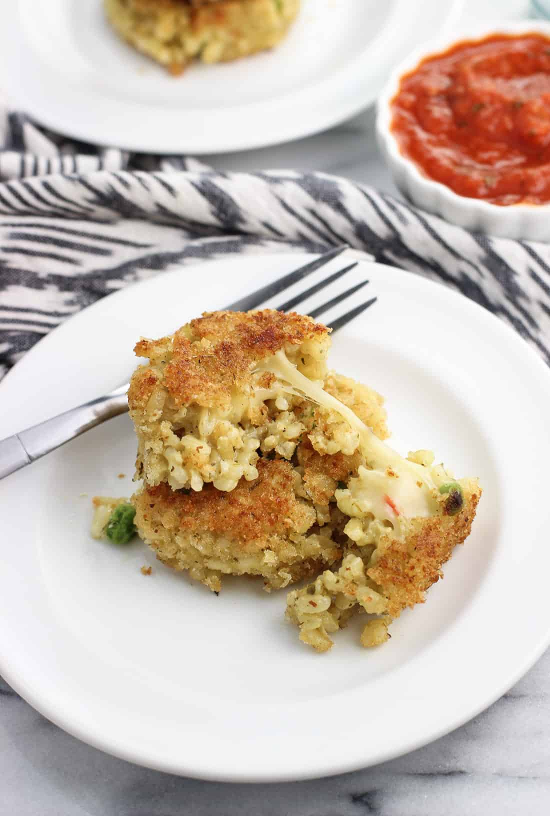Two risotto cakes in a stack with the top cake cut in half to see the cheese pulling out