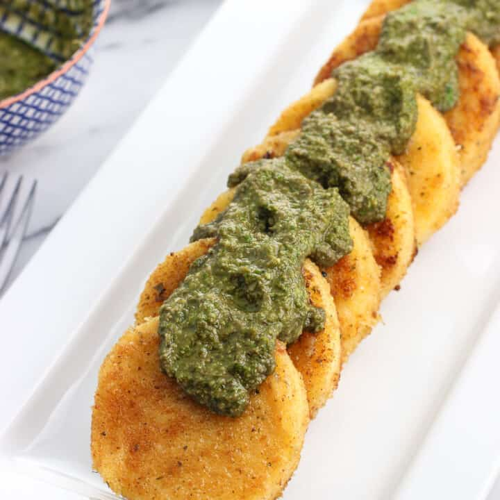 Polenta slices on a serving tray with dollops of basil pesto over top
