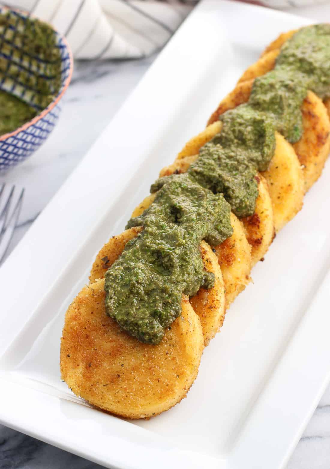 Pan fried tubed polenta slices arranged in a row on a serving tray topped with basil pesto dollops