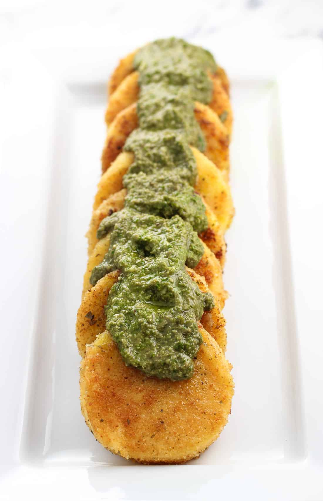 Pan fried polenta on a tray with basil pesto spooned over top