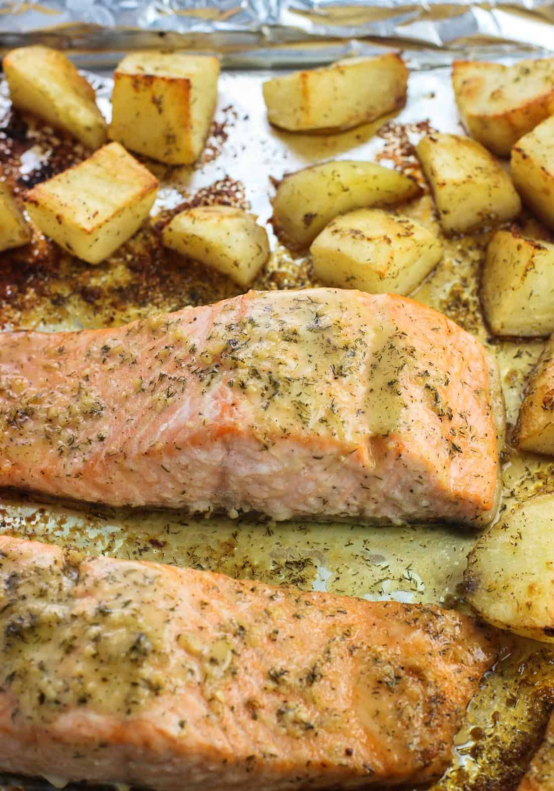 Two cooked salmon fillets coated in horseradish sauce on a foil-lined baking sheet surrounded by potato wedges