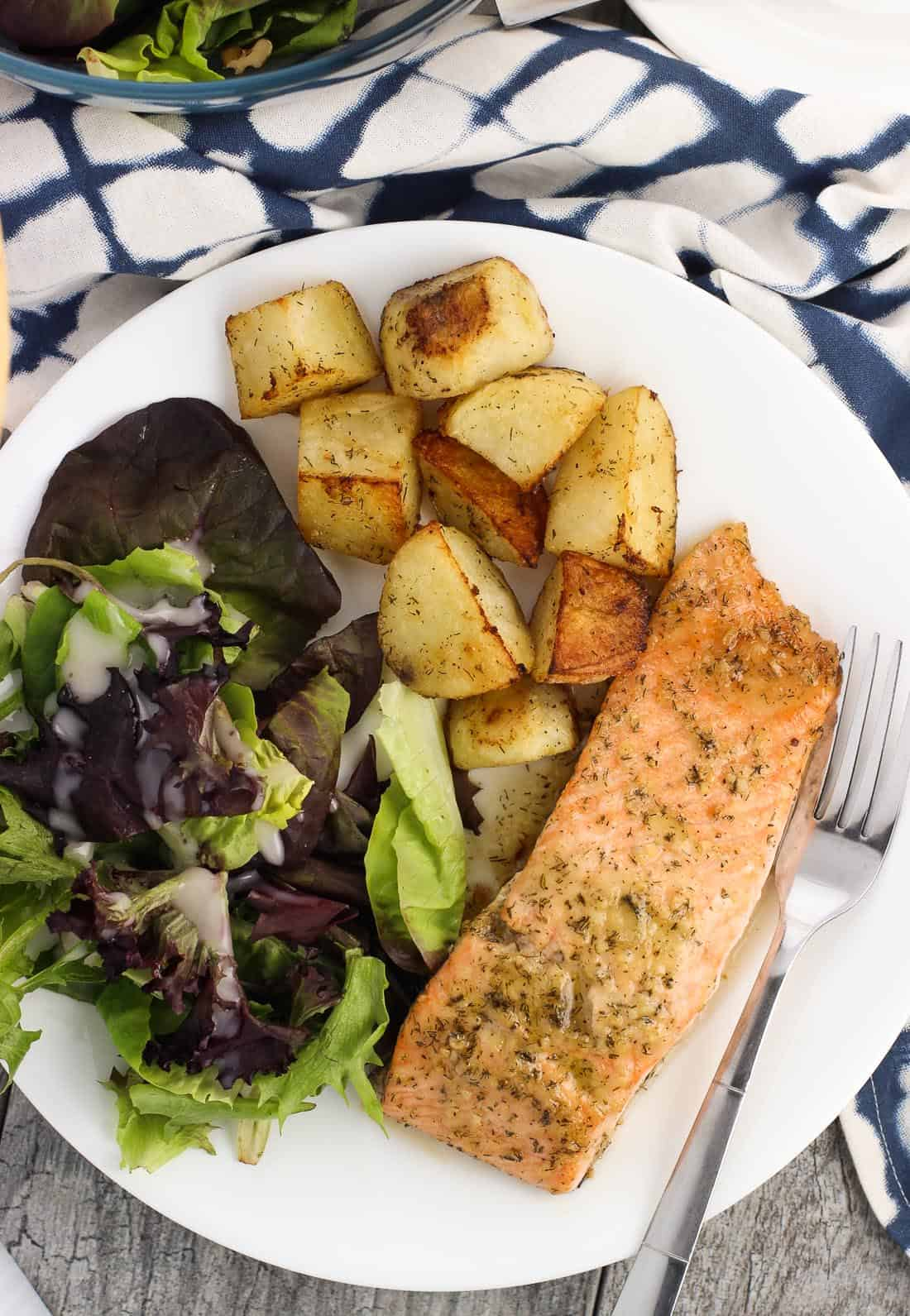 An overhead view of a salmon fillet, potato wedges, and a side salad on a dinner plate with a fork