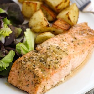 A dinner plate of a salmon fillet coated in horseradish sauce, roasted potato cubes, and a side salad