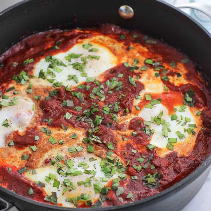 Shakshuka with four eggs in a tall-sided skillet topped with herbs with a small bowl of hummus in the background