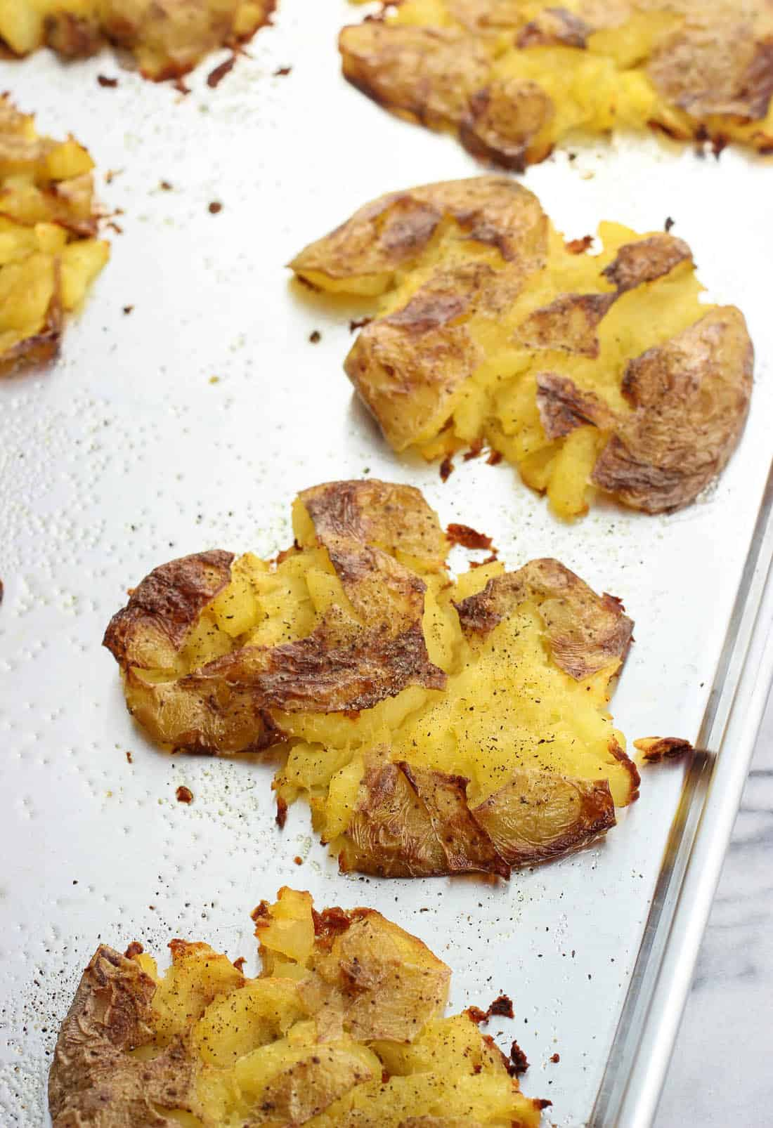 Crisped smashed potatoes on a greased metal baking sheet