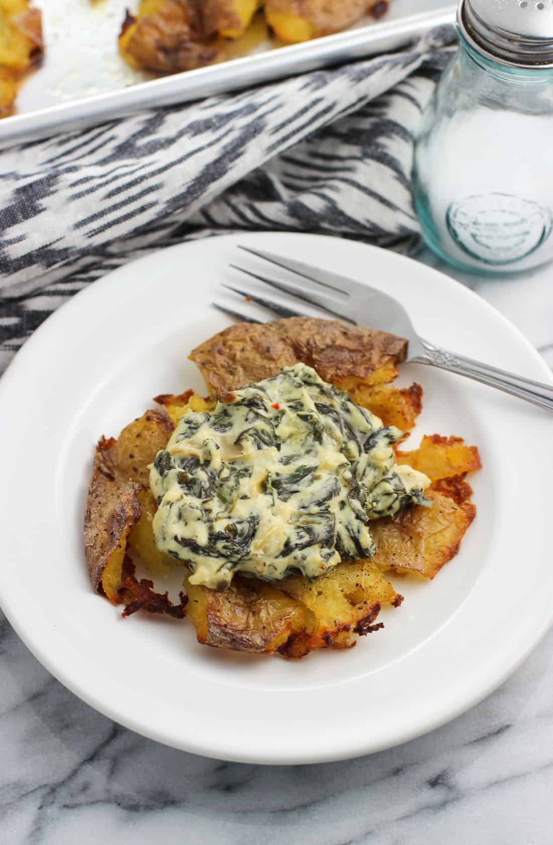 A smashed potato on a small appetizer plate topped with spinach artichoke dip