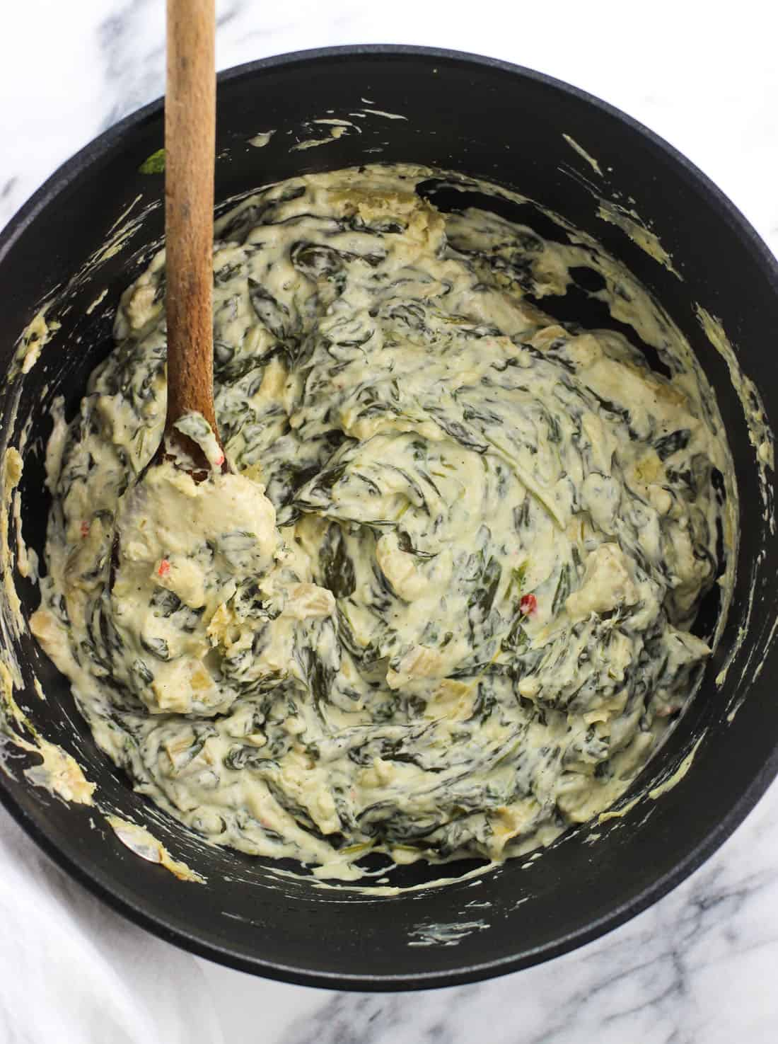 A medium saucepan filled with spinach artichoke dip with a wooden spoon