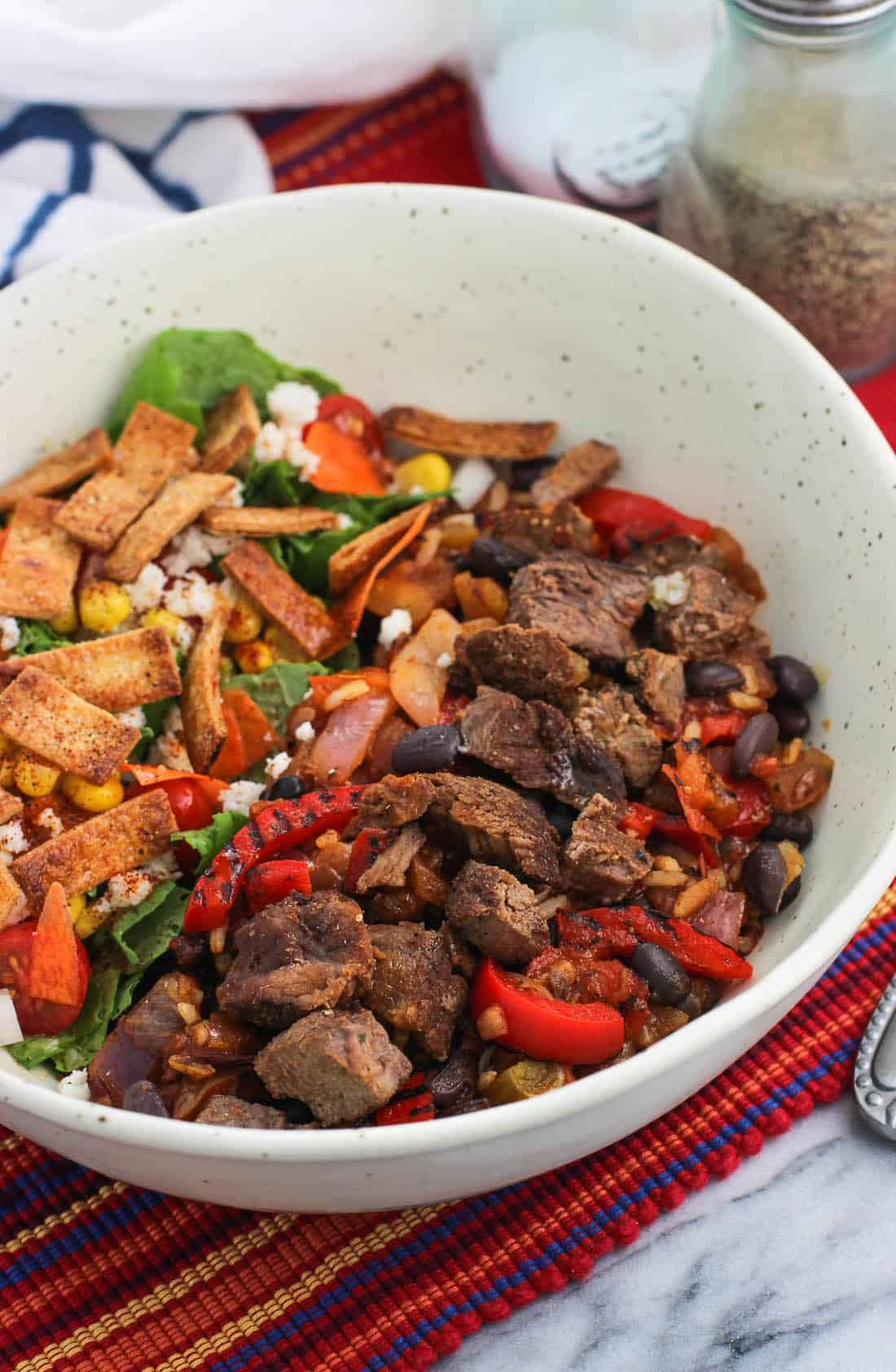 Barbacoa beef and peppers in a bowl next to a salad with salt and pepper shakers in the background