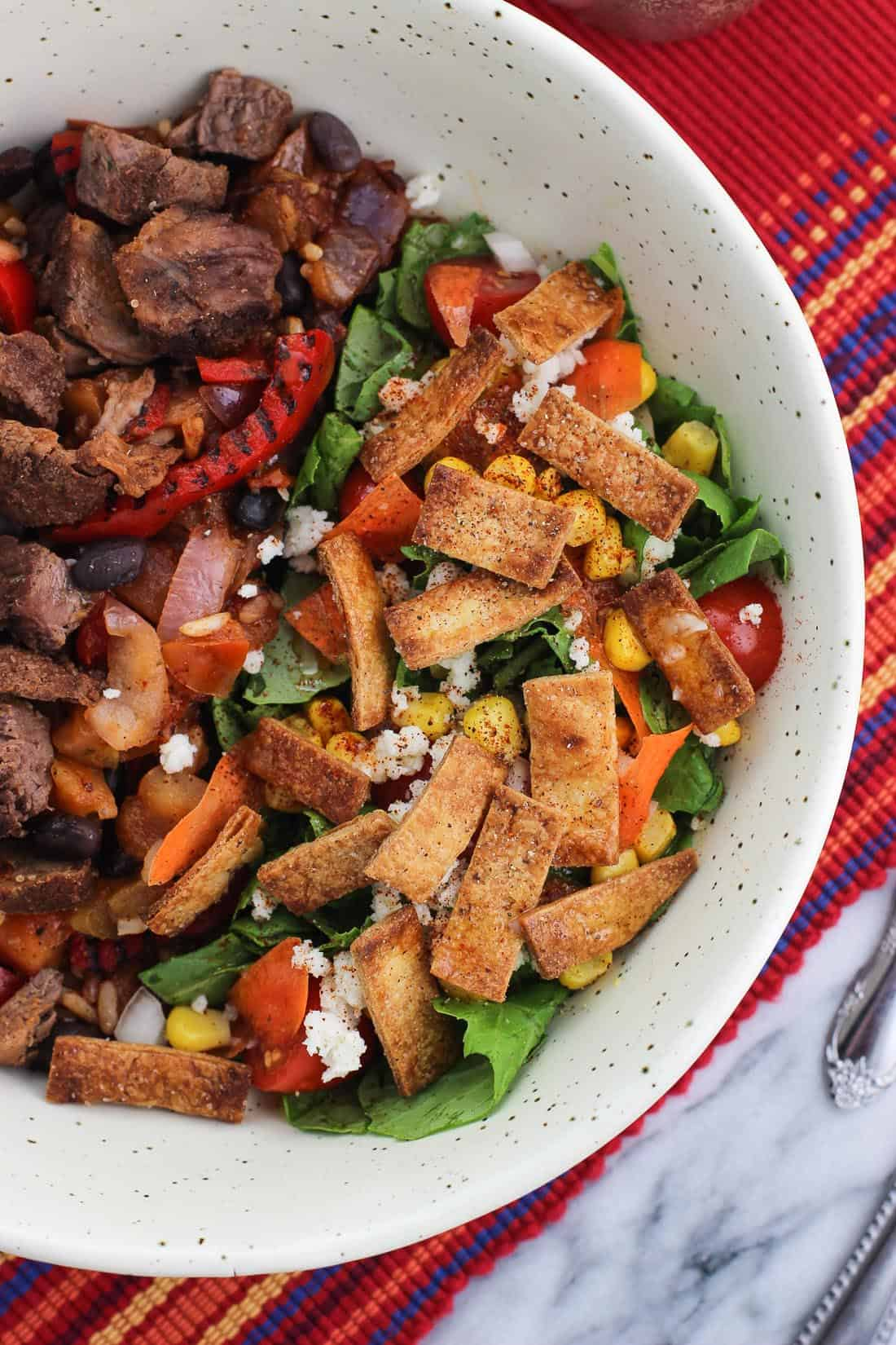 A side salad topped with tortilla strips in a bowl with steak and peppers