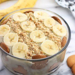 A round glass dish of a layered banana pudding dessert.