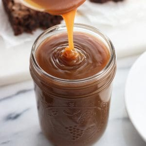 Caramel sauce being poured into a glass mason jar with a batch of brownies on a board in the background