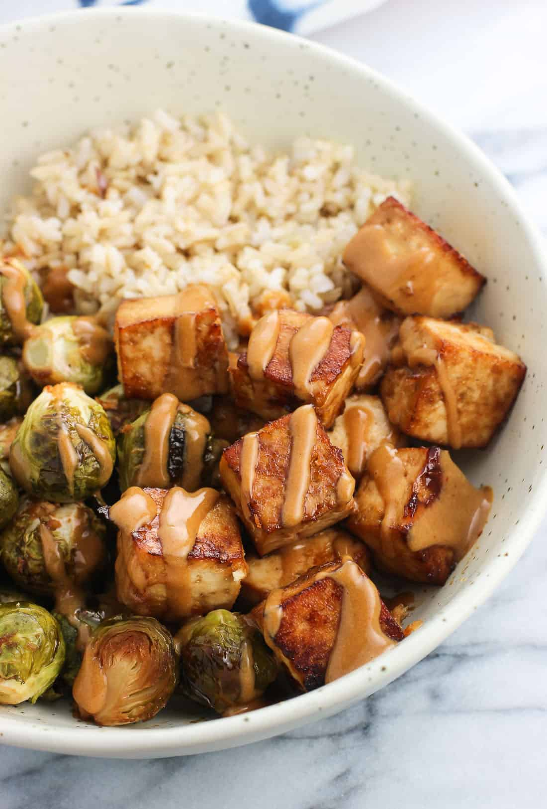 A bowl of baked tofu and roasted brussels sprouts halves drizzled with peanut sauce served with brown rice