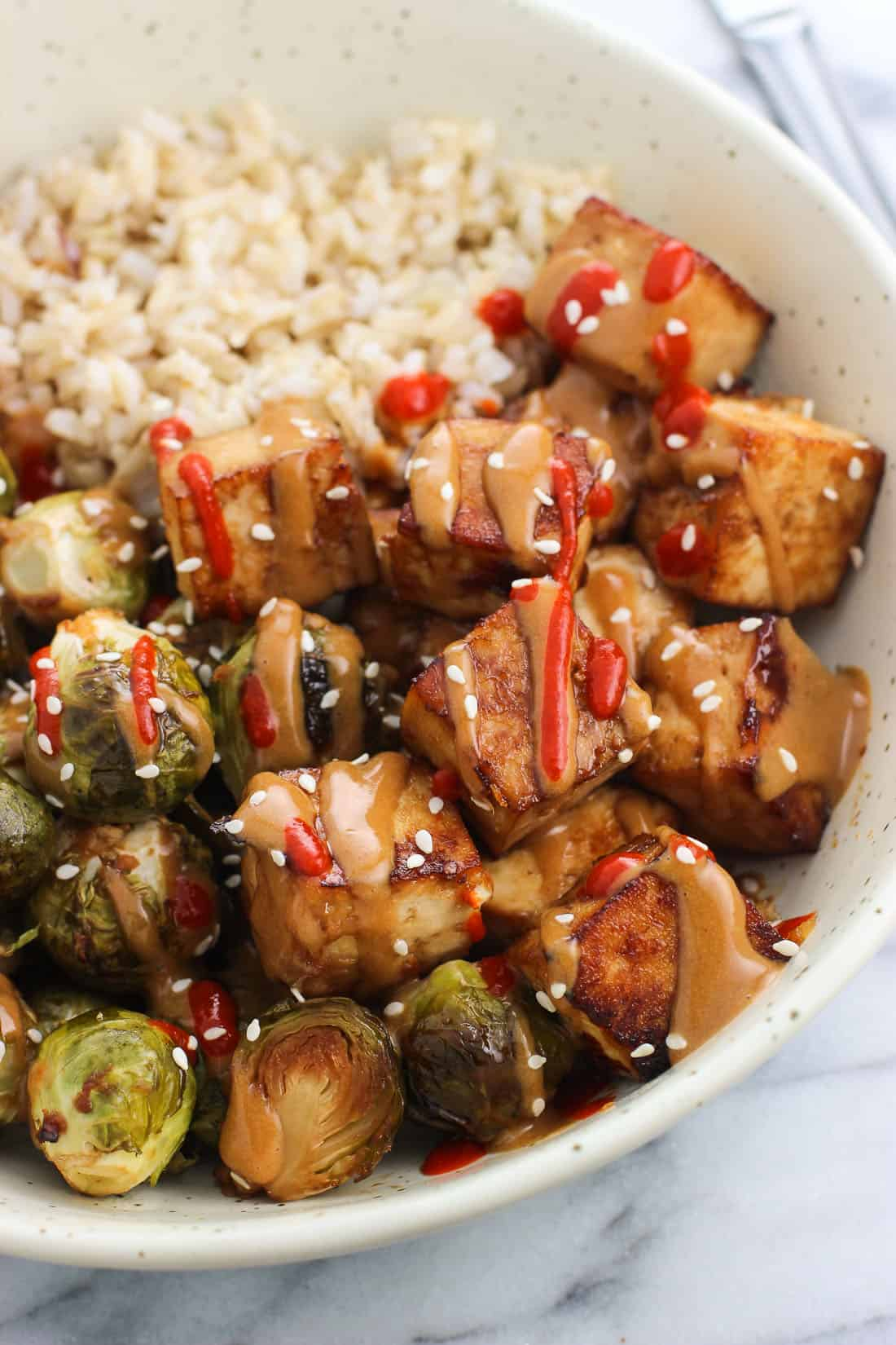 A close-up of roasted tofu cubes and brussels sprouts drizzled with peanut sauce and sriracha, served next to brown rice