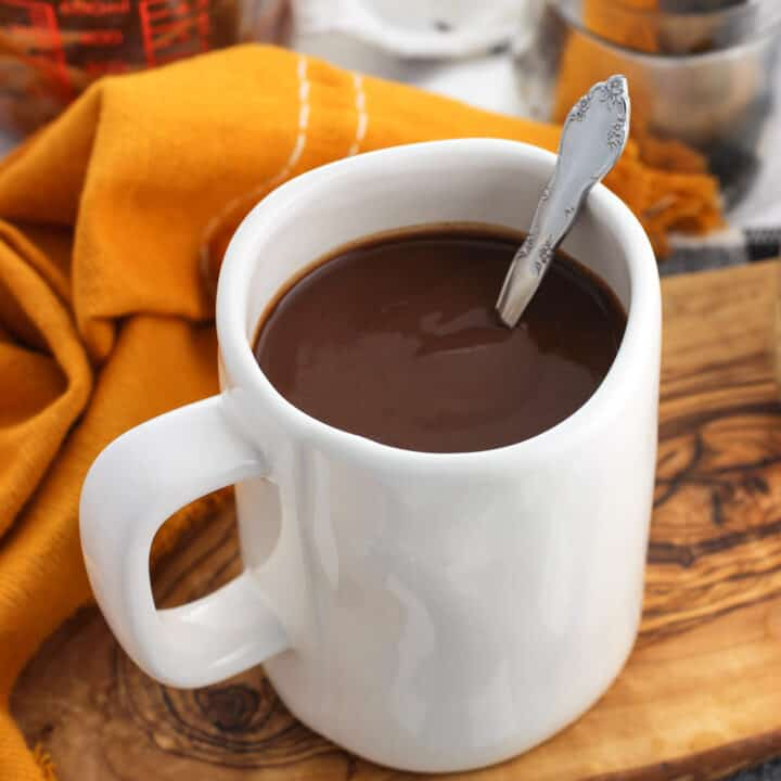 A large mug of hot chocolate with a spoon in it on a wooden tray.