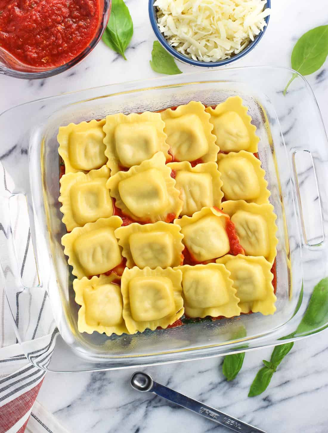 Spinach, sauce, and ravioli layered in a square glass baking dish.