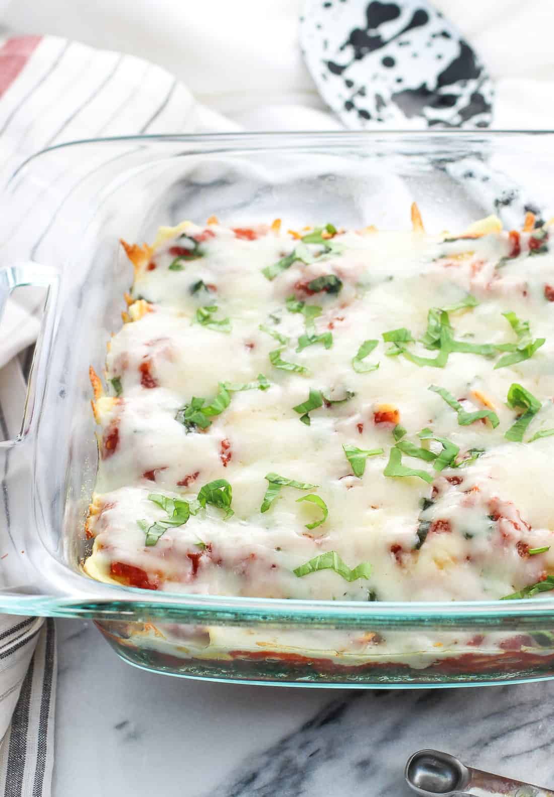 A glass baking dish filled with spinach, ravioli and marinara sauce, topped with melted mozzarella and fresh basil