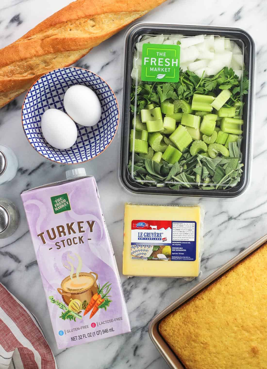 Recipe ingredients on a marble board, including a baguette, eggs, celery, herbs, onion, Gruyere, a carton of turkey stock, and a pan of cornbread