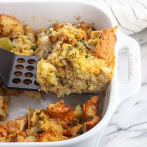 A slice of strata being lifted out of the baking dish by a spatula
