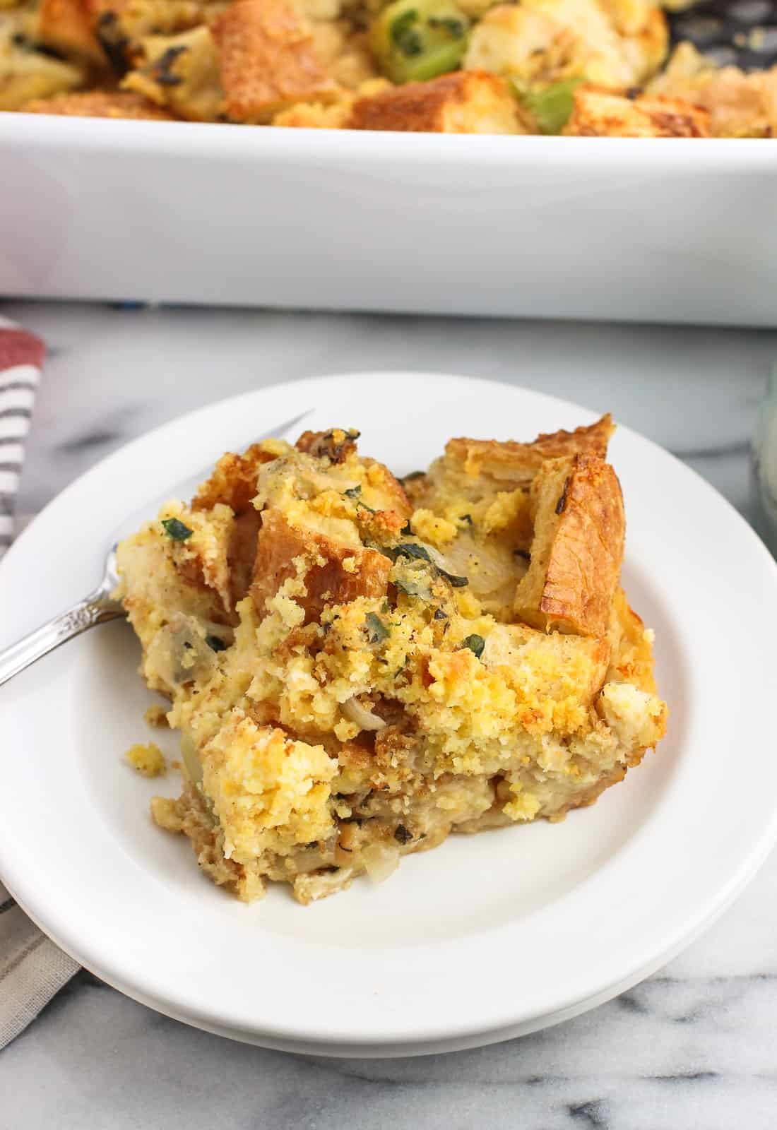 A slice of cornbread strata on a small plate with a fork with the whole pan in the background